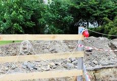 rote und weiße Bandlaterne auf dem Zaun, der den Abzugsgraben begraben im Boden einschließt Lizenzfreie Stockfotografie