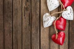 Rote und weiße hölzerne Herzen auf altem braunem hölzernem Hintergrund Stockbilder