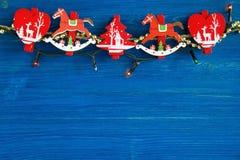 Rote und weiße hölzerne Weihnachtsdekorationen und Weihnachtslichter auf dem blauen hölzernen Hintergrund Lizenzfreie Stockfotografie