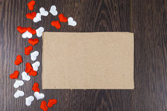 Rote und weiße Herzen und Karte auf einem dunklen hölzernen Hintergrund Stockbild