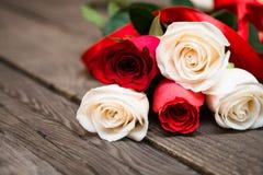 Rote und weiße Rosen auf einem dunklen hölzernen Hintergrund Tag Women s, V Lizenzfreies Stockfoto