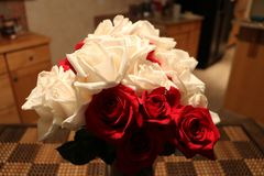 Rote und weiße Rosen-Blumenstrauß in einem Ausgangsinnenraum lizenzfreie stockfotografie