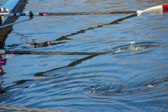Rote und weiße Ruder, die im Wasser unsynchronisiert spritzen Lizenzfreie Stockfotos
