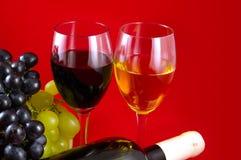 Rote und weiße Weine und Trauben. Lizenzfreies Stockfoto