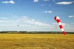 Rote und weiße Windsockwindsocke auf blauem Himmel, gelbem Feld und Wolkenhintergrund stockfotos