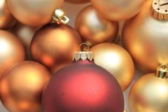 Rote Verzierung auf einem Stapel von goldenen Verzierungen Stockfotografie