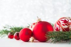 Rote Verzierungen und Weihnachtsbaum auf Funkelnfeiertagshintergrund Frohe Weihnacht-Karte Stockbild