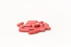 Rote Vitamintabletten auf einer weißen Oberfläche Stockfotografie