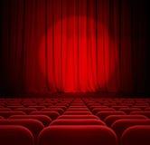 Rote Vorhänge des Theaters oder des Kinos mit Scheinwerfer und Sitzen Lizenzfreie Stockfotos