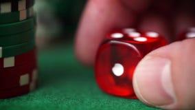Rote Würfel in der Hand und Kasinochips auf grüner Tabelle stock footage