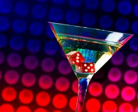 Rote Würfel im Cocktailglas auf buntem Steigung bokeh Stockbild