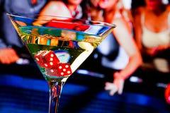 Rote Würfel im Cocktailglas vor Spieltisch Stockbilder