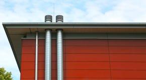 Rote Wand eines modernen Gebäudes mit Lüftungsrohren lizenzfreie stockfotos