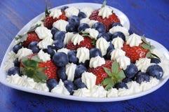 Rote, weiße und blaue Beeren mit frischer Schlagsahne spielt Nahaufnahme die Hauptrolle Stockbilder