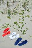 Rote weiße und blaue Flipflops auf dem Strand Lizenzfreie Stockbilder