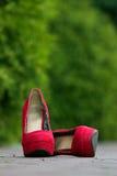 Rote weibliche Schuhe auf einem cobbled Fußweg im Park Lizenzfreies Stockbild