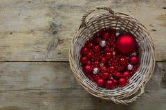 Rote Weihnachtsbälle und -flitter in einem Korb auf einem rustikalen hölzernen t Lizenzfreies Stockfoto