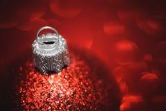 Rote Weihnachtsballnahaufnahme auf Funkelnhintergrund Lizenzfreies Stockfoto