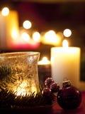 Rote Weihnachtsballverzierungen mit brennenden Kerzen (flache Tiefe Stockbild