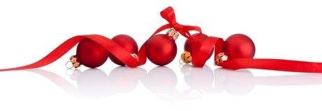 Rote Weihnachtsbälle mit dem Bandbogen lokalisiert auf weißem Hintergrund Lizenzfreie Stockfotos