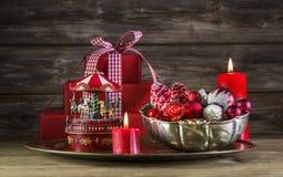 Rote Weihnachtsdekoration auf hölzernem Hintergrund mit Karussell Stockbild