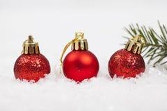 Rote Weihnachtsdekorationen auf Schnee lizenzfreie stockfotografie