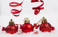 Rote Weihnachtsdekorationen auf Schnee lizenzfreie stockbilder