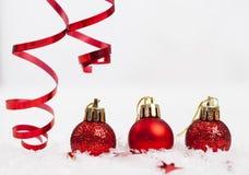 Rote Weihnachtsdekorationen auf Schnee stockfotos