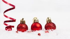 Rote Weihnachtsdekorationen auf Schnee lizenzfreies stockbild