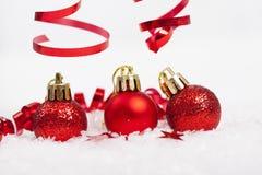 Rote Weihnachtsdekorationen auf Schnee lizenzfreies stockfoto