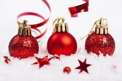 Rote Weihnachtsdekorationen auf Schnee stockbilder