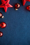 Rote Weihnachtsdekorationen spielt und Bälle auf dunkelblauem Segeltuchhintergrund die Hauptrolle Frohe Weihnacht-Karte Stockfotografie