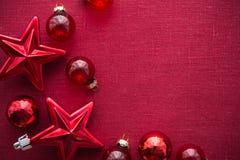 Rote Weihnachtsdekorationen u. x28; Sterne und balls& x29; auf rotem Segeltuchhintergrund Frohe Weihnacht-Karte Stockfoto