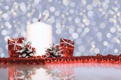 Rote Weihnachtsdekorationen und -kerzen auf einem lila Hintergrund Lizenzfreie Stockfotografie