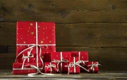 Rote Weihnachtsgeschenke auf einem alten hölzernen braunen Hintergrund Stockfotografie