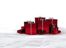 Rote Weihnachtsgeschenke im Schnee Lizenzfreie Stockfotos