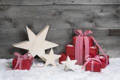 Rote Weihnachtsgeschenke mit hölzernen Anfängen auf grauem hölzernem Hintergrund Stockbild