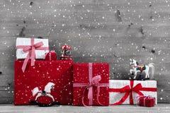 Rote Weihnachtsgeschenke und Geschenkboxen mit Schaukelpferd auf Grau Stockbild