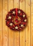 Rote Weihnachtsgirlande in der alten hölzernen Tür Stockfotografie