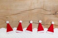 Rote Weihnachtshüte auf hölzernem Hintergrund für eine Grußkarte Stockfotos