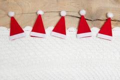 Rote Weihnachtshüte auf hölzernem Hintergrund für eine Grußkarte Lizenzfreies Stockfoto