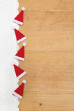 Rote Weihnachtshüte, gewirkter Schnee auf hölzernem Hintergrund Lizenzfreies Stockbild