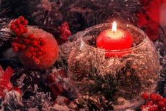 Rote Weihnachtskerze in einem Glas auf dem Hintergrund von Weihnachtsdekorationen im Schnee Lizenzfreie Stockfotografie