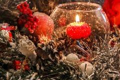 Rote Weihnachtskerze in einem Glas auf dem Hintergrund von Weihnachtsdekorationen im Schnee Lizenzfreies Stockfoto