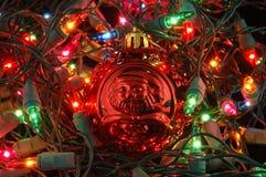 Rote Weihnachtskugel in den Weihnachtsleuchten lizenzfreie stockfotos