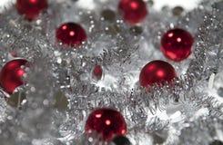 Rote Weihnachtskugel in der silbernen Girlande Lizenzfreie Stockbilder