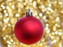 Rote Weihnachtskugel gegen goldenen Hintergrund Lizenzfreie Stockfotos