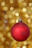 Rote Weihnachtskugel gegen goldenen Hintergrund Lizenzfreies Stockfoto