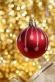 Rote Weihnachtskugel gegen goldenen Hintergrund Lizenzfreies Stockbild
