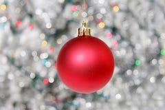 Rote Weihnachtskugel gegen silbrigen Hintergrund Lizenzfreie Stockfotos
